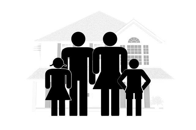 obrázek rodičů a dětí v popředí s šedým domem za zády