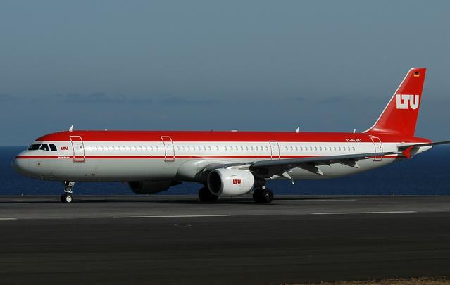 červenobílé letadlo stojící na letišti.jpg