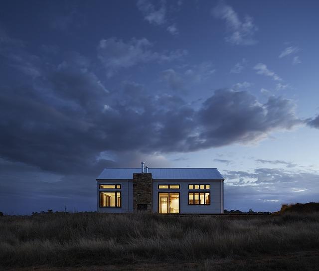 dům, před domem suchá vysoká tráva, stmívá se, uvnitř se svítí, komín vepředu