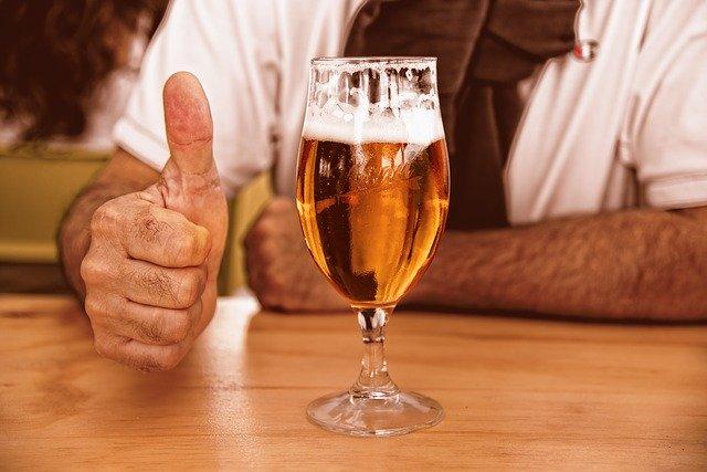 muž u stolu se sklenicí piva